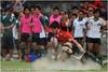 成功大學選手在台灣大學選手替補區前遭擒抱. 南北名校於分組預賽中強碰,兩隊互不相讓,最後台大以17:5拿下比賽勝利.(2011/5/14)
