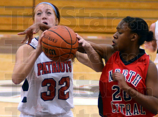 Tribune-Star/Jim Avelis<br /> Hacked: Terre Haute North's Sierra Sykes gets fouled by North Central guard Shelbi Owens.