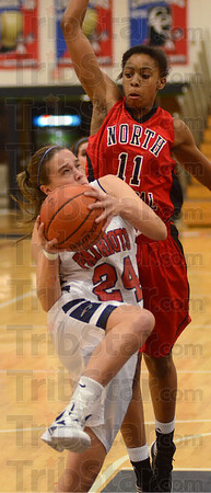 Tribune-Star/Jim Avelis<br /> Trouble looming: Terre Haute North guard winces as she tries to put up a shot against the defense of North Central's Celewcte Edwards in second quarter action Thursday night in the Patriot's gym.