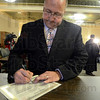 Tribune-Star/Jim Avelis<br /> Making it official: Norman Loudermilk, (D) 3rd, signs his name to the certificate after taking the oath of office for another term as Terre Haute City Councilman.