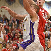 Tribune-Star/Jim Avelis<br /> Inside job: Caleb Turner penetrates the paint as Marshall's Taylor Maurer tries for the block.