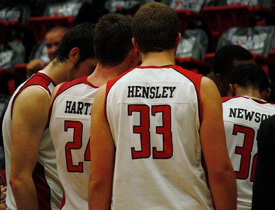 Number 24, Kevin Hartley and Number 33, Corey Hensley listen to Coach Holtman with the rest of the team, during a time out.