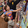"Tribune-Star/Jim Avelis<br /> Big helper: Terre Haute police Sgt. Bill Sheldon helps Tyana and Paula Stanton sort through the toys at Walmart east during their""Kids shopping with Police"" time early Sunday morning."