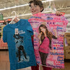 "Tribune-Star/Jim Avelis<br /> Which one: Tyana Stanton holds up t-shirts so her parents, April and Andrew, can help her choose the one to get, The three, along with Tyana's sister Paula were taking part in ""Kids shopping with Police"" early Sunday morning at the east side Walmart."