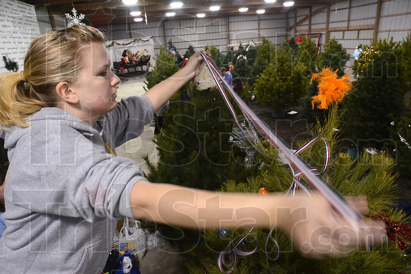 Tribune-Star/Jim Avelis<br /> Just enough: Victoria Trench stretches ribbon over the tree she is helping decorate. Indiana State University President Emeritus Lloyd Benjamin sponsored the tree.