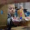 Tribune-Star/Joseph C. Garza<br /> He's got the bread taken care of: Elijah Riley loads two loaves of bread into one of the Tribune-Star Christmas baskets at the newspaper's production facility Friday.