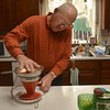 Tribune-Star/Joseph C. Garza<br /> By hand: Jerry Lehman separates the pulp of persimmons from the skin and seeds at his home on Dec. 8. Lehman freezes the pulp and uses it to make various baked goods.