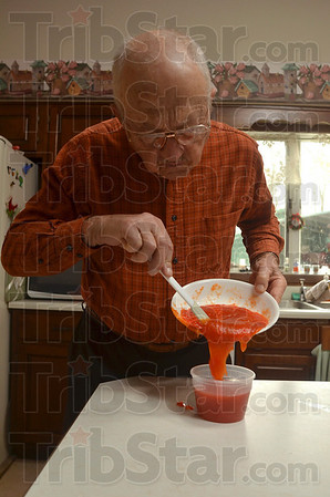 Tribune-Star/Joseph C. Garza<br /> Ready for the freezer: Jerry Lehman scrapes persimmon pulp into a container for storage in his freezer Dec. 8 at his home.