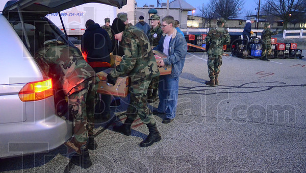 Tribune-Star/Jim Avelis<br /> Loading: Members of the Terre Haute North High School AFJROTC were on hand early Chhristmas Eve to load food basket into volunteers vehicles.
