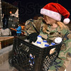 Tribune-Star/Jim Avelis<br /> Ho Ho homogenized: Early Saturay morning Kenna Jenkins of the Terre Haute North High School AFJROTC loads milk into a truck delivering Tribune-Star Christmas baskets. Some 200 volunteers were involved this year.