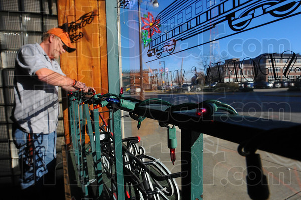 Tribune-Star/Jim Avelis<br /> Let there be lights: Carl Tresner, general manager of The Terminal, strings Christmas lights in the front window of the downtown watering hole Wednesday afternoon.
