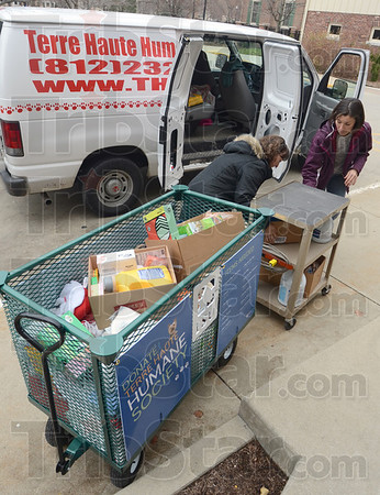 Tribune-Star/Jim Avelis<br /> Helping hand: Maggie Wheeler, English instructor and Outreach Co-ordinator at Indiana State University helps Jessica Hoffman, Operations Manager at the Terre Haute Humane Society unload donations for the animanls there. ISU collected two carts worth of animal tiays and food as well as office and cleaning supplies.