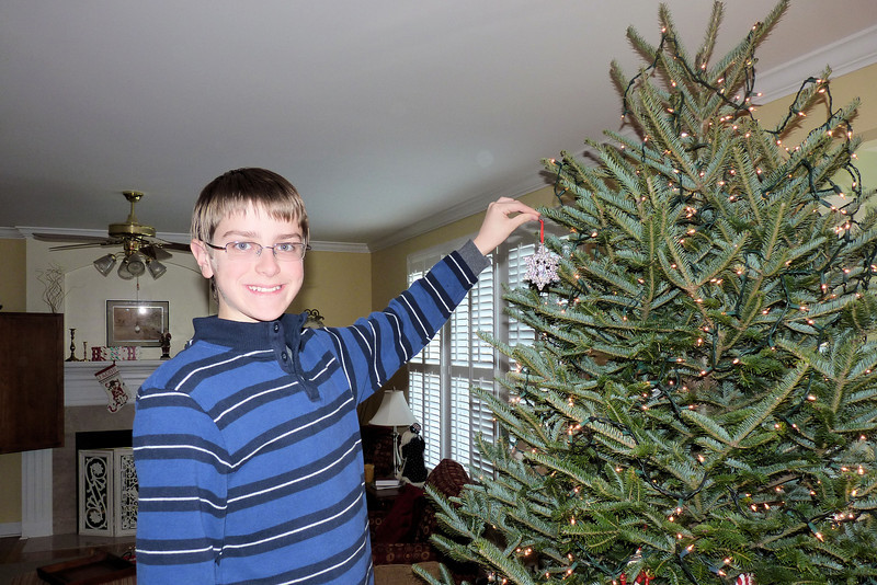 Anthony, hanging Mom's ornament on the tree