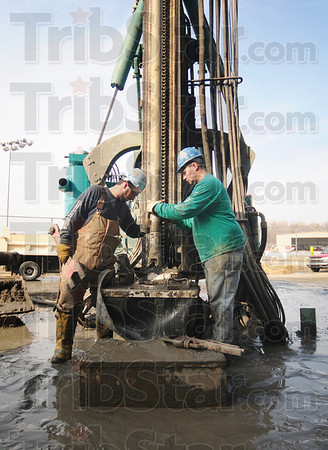 Tribune-Star/Rachel Keyes<br /> Guiding Hand: Operator Travis Gregg (left) and Comboman Mike Lang (right) guide the drill bit into the shaft for another round of drilling.