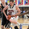 """Driven: North's #50 Justin Gant drives the ball to the basket against Carmel's 6' 10"""" center Alec Peterson Friday night."""