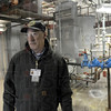 Tank: Facilities manager Roger Dagley is seen in the mechanical room of a housing unit with the water tank that will be heated by the solar panels being installed.