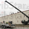 Solar panels: A construction crew working at the Wabash Valley Correctional Institute uses a crane to move solar panels and necessary hardware to the roof of a housing unit Tuesday.