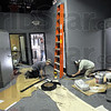 Trim: Workers apply base board trim around the walls in the rear portion of the new Century 21 office in the former Children's Museum space Friday afternoon.