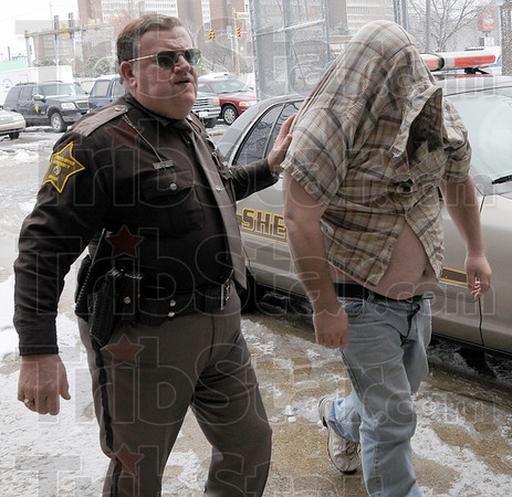 Arrested: Vigo County sheriff's deputy Norman Cottrell escorts Lyman Roberts into the jail Friday morning. Roberts is charged with several counts of home improvement fraud.