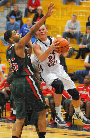 """Tribune-Star/Jim Avelis<br /> No fear: Logan Shipley takes the ball inside against the defense of Lawrence North's 6'10"""" center Michael Chandler. Shipley drew a foul on the play."""