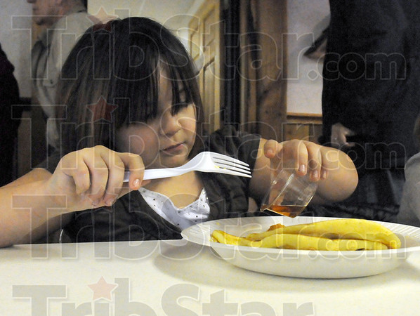 Syrup: Nine-year-old Adriana Wallace pours maple syrup over her pancakes and sausage Saturday morning at Fowler Park.