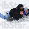 Yippe!: Father Kevin Johnson(top) slides down the Deming Park hill on and intertube with sons Mahki Johnson (left) and Ty Johnson (right) Saturday afternoon.