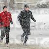 Snow men: Todd Brinza and Matt Scamihorn run through snow flakes along Ohio Blvd. Saturday afternoon in spite of the heavy snowfall.