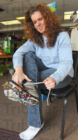 Tribune-Star/Jim Avelis<br /> In demand: The Element Outdoor Outfitters store at 11th and Wabash saw high demand for the Yak Trax brand of ice cleats since the freezing rain hit last Tuesday. They have recieved additional shipments after their stock ran out mid-week.  Here store owner Stepahanie McCay laces up a pair of running shoes  with the cleats already on.