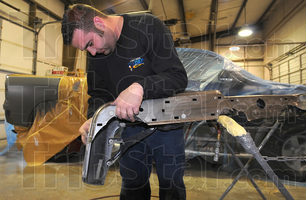 Tribune-Star/Jim Avelis<br /> A little off the side: Jeremy Busenbark, an employe at Honey Creek Collision, sands a bumper to get it ready for painting. The collision repair business has seen more customers due to fender beneder accidents since the icy weather arrived.