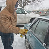 Tribune-Star/Jim Avelis<br /> Team effort: Doug Wright, Regional Hospital Director of Process Improvement, uses a chemical de-icer before scraping ice from a fellow employee's windows. Employee volunteers were out in the hospital parking lots making it a little easier for co-workers to deal with the inclement weather.