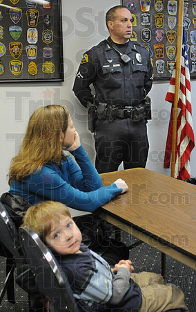 My dad: Four-year-old Luke Ellerman checks all the media as he waits for his fathers promotion ceremony at police headquarters Monday. He's attending the ceremony with his mother Donna Ellerman. His father Mike Ellerman is being promoted to sergeant.