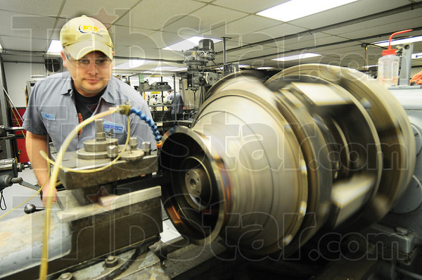 Tribune-Star/Rachel Keyes<br /> Grind It Out: Machinist Paul Majors Machines parts to for a turbine engine.