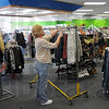 Coming soon: Goodwill store employee Bridgette Manning puts clothing on racks as she helps prepare the new store for opening.