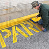 "Parking prep: Goodwill Store employee Marlin Crouse puts a fresh coat of paint on the ""no parking"" signs painted on the lot of the new Goodwill facility on south Third Street."