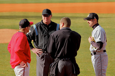 Coach Rusty Stroupe meets his opposition and umpires before the home opener.