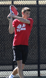 Julien Belair plays in a doubles match against the Trojans.