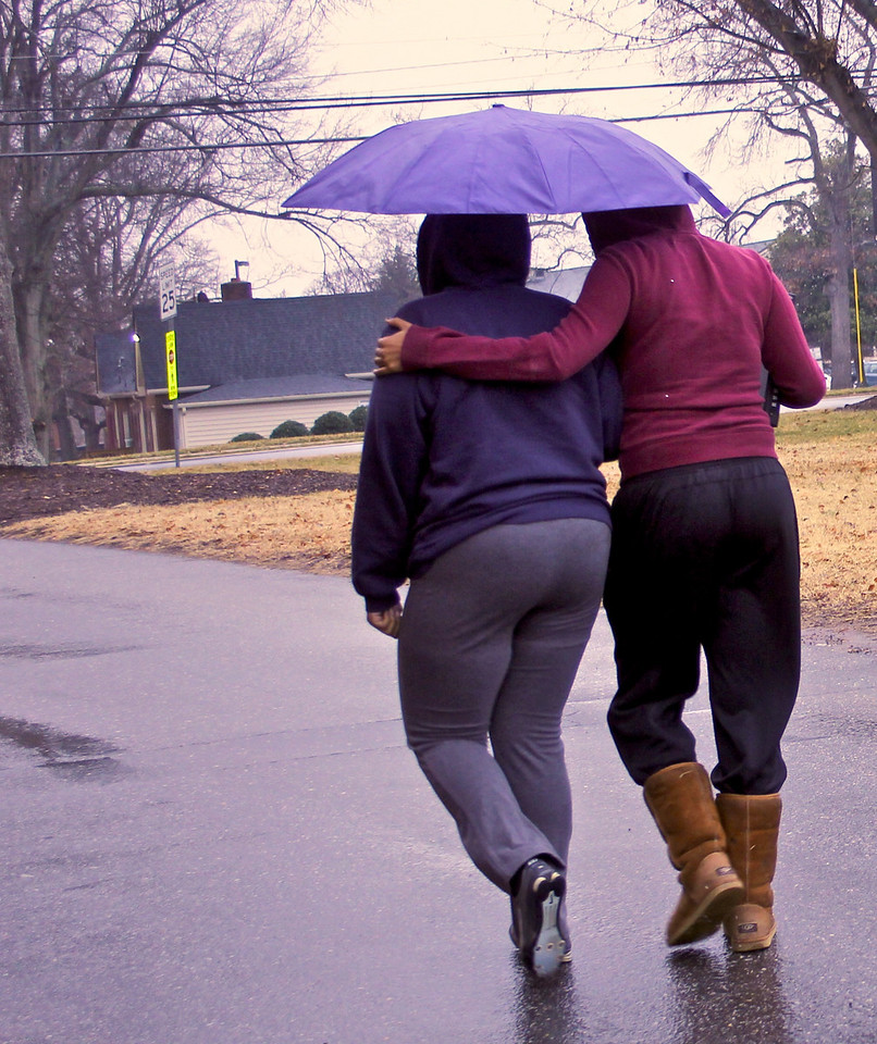 Friends share an umbrella on a cold, rainy day at GWU.