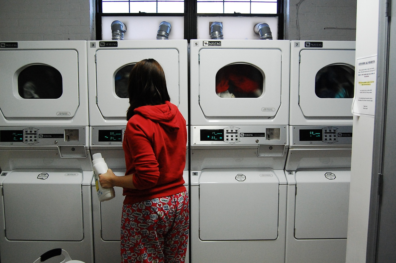 Typical for a college student on a rainy day, Hannah Rolen checks the settings for her laundry.