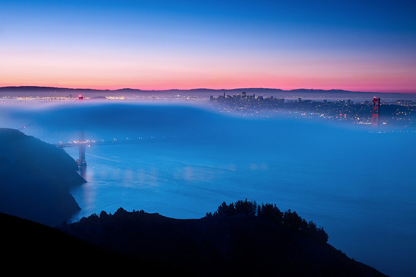 I've been wanting to get foggy photos of the Golden Gate Bridge (GGB) for a while now. I've seen some amazing photos of the bridge by several local photographer's (like Chris Honeysett, JaveFoto, etc) and I've wanted to get out there and try to re-create and capture my own. Despite coming down with a cold this week I woke up at 4:15am and headed up to Hawk Hill with Willie. When we arrived the gate was completely clear -- no fog at all! As we pulled into the parking lot a cop was sitting at the entrance and turned his light on when we pulled in but didn't say anything. Finally as we started unpacking our camera gear he turned his spotlight on us and I went over to find out that he wouldn't let us park/walk up Hawk Hill (which was closed until sunrise).   Fortunately the road up Hawk Hill opened before sunset and we got up there in plenty of time to walk up the hill before sunset. Unfortunately, as we started walking we noticed that the bridge was becoming completely covered in fog! Our hopes at low fog, below the bridge, was completely dashed. We walked up anyways, setup up our cameras, and hoped that there would be a part in the fog to give us something to photography.  Fortunately the fog had some gaps in it and we were able to snap off a couple photos while the bridge went from being completely enveloped to completely clear. Yes, all this fog did go away as the sun started to come up. I threw on a 3-stop reverse ND Grad filter to bring out all the color in the sky.   At one point I went to put an extra 2-stop ND grad into my Lee Filter holder but it slipped threw the holder and fell on the other side of the fence and down the slope! It stopped before rolling all the way down and I risked jumping over the fence to get it. Unfortunately the fence was too tall for me to get back over and I had to walk all the way around to get back!   Nikon D300s w/Nikkor 24-70mm f/2.8G ED AF-S 27mm, f/11, 30 seconds, ISO 200, Feisol Tripod HiTech 3-stop ND Grad