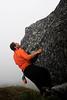 Kelsey works some moves on a boulder in the fog.
