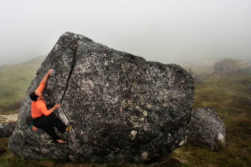 Kelsey works some moves on a boulder in the fog.