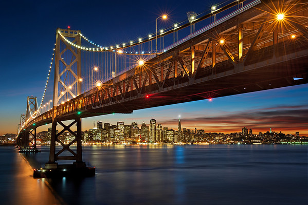 """Willie and I have been wanting to take the (now popular) San Francisco skyline photo from under the Bay Bridge for a while now. The photo is much much nicer during the holiday time when 17,000 lights outlining the Embarcadero Center buildings are turned on and a bright white light (called The Beacon) is turned on at the Transamerica Building (the triangular building). Willie had been checking the SF webcams and it looked like The Beacon was being lit each night. Last year it had been lit by this time of year so we thought we should be pretty safe in making sure The Beacon would be lit.   We left work early and headed out to Treasure Island with plenty of time to find parking, hike up the hill, find """"the spot"""" and then get setup. Unfortunately when US-101 and I-280 merged we hit a HUGE Friday afternoon holiday traffic. We arrived at Treasure Island much much later than planned (almost an hour later), and had to high tail it up the hill and over the Bay Bridge (we were both sweating pretty badly). After hopping the guard rail we actually found the spot pretty easily (just as we were walking over the Bridge a CalTrans truck drove by and screamed over the loud speaker """"No photographs from this side of the bridge."""" We kept walking). We scouted out the area for a while, found our spots and then waited for the light to get nice.  When I originally composed this image I wanted to make the SF Cityscape as large as possible, which meant that I clipped off some of the lights on the Bay Bridge. Once it got dark enough I realized that I really did want to include the extra light on the Bridge and I had zoom out and recomposed to get this final composition.  Luckily for us there was an absolutely BEAUTIFUL sunset that night, which makes the photo much more interesting. Unfortunately though, as the sun began to set we noticed that the Transamerica Beacon was NOT going to turn on :(. The city lights started to come on, then the 17,000 Embarcadero Center lights were visible but The """