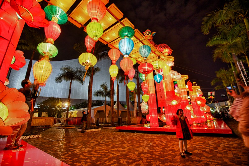 A girl poses for photos in front of an illuminated Chinese lantern display set up for the Chinese New Year festivities just next to Kowloon Public Pier.