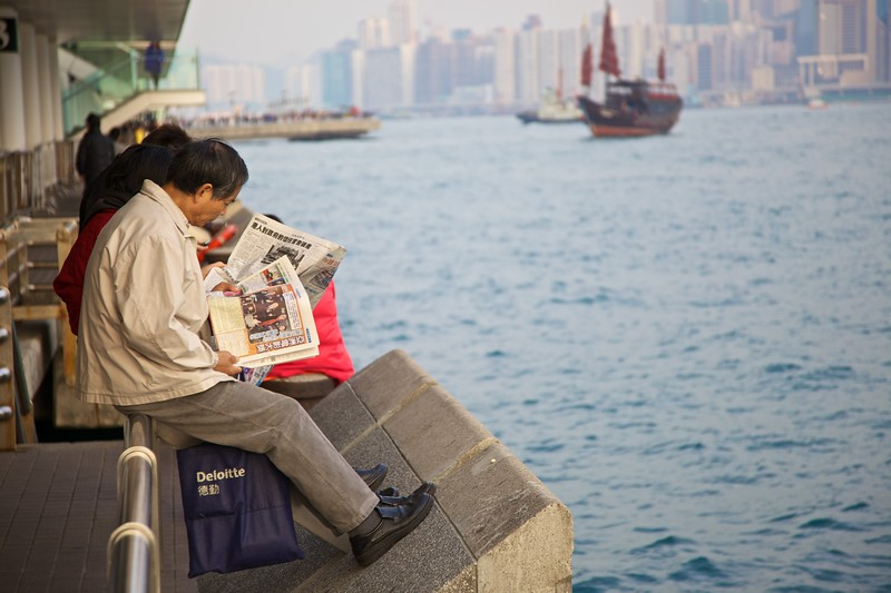 A man catches up on the day's news on the waterfront at Kowloon Public Pier.