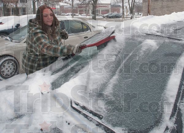 Brush it Off: Samantha Frantz brushes the snow of her car in the mid morning hours on January 20th.