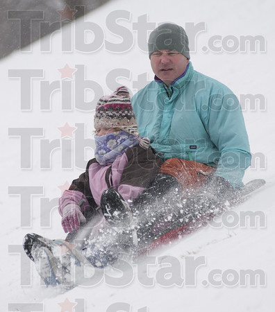 Downhill slide: Brent Denny slides down the Deming Park hill with seven year old daughter Chloe bundled up in front.