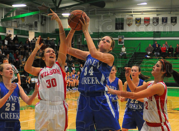 Tall order: Lindley Higham(34) snares a rebound for the Honey Creek team. Defending are Warriors Paxton Granda(30) and Mandee Eberle(42).