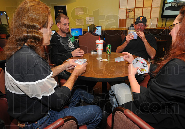 Hearts in their hands: Club Soda partiers Jerry Wilkey, Bobby Wright, Mike Black and Jamie Graves play a game of Hearts waiting for the New Year's Eve celebrations to begin Friday night.