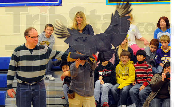 Tribune-Star/Jim Avelis<br /> Bait: Dixie Bee Elementary School teacher Tim Moss recieves Buzz, a black vulture as part of the Birds of Prey program put on by the American Eagle Foundation.