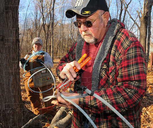 Snip and splice: Bud Montgomery assembles the sections of sugar water line that will collect the sap from maple trees in Prairie Creek park this Spring. With him is Kara Kish, Assistant Superintendant of the Vigo County Parks.